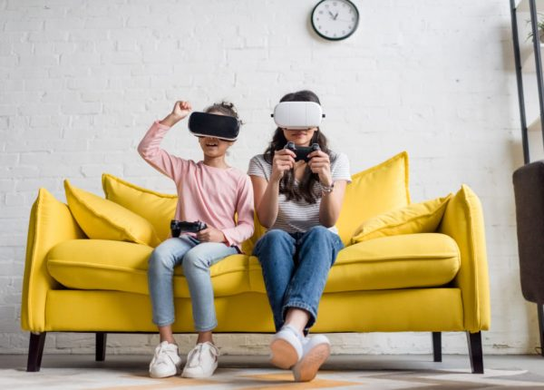 mother and daughter in vr headsets playing video games at home on couch